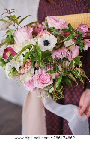 Young Female Florist Holding A Freshly Made Blooming Floral Bouquet Of Pastel Pink Carnations And Eu