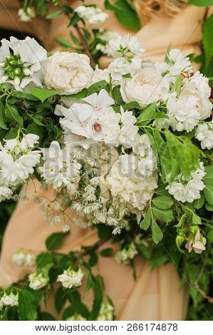 Flower Arrangement Of White Flowers On The Dress. Bride Holds A Wedding Bouquet Close-up