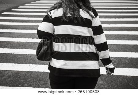 Black And White Manhattan Street Scene. Fat Woman Wearing Black And White Striped Sweater Crosses Th
