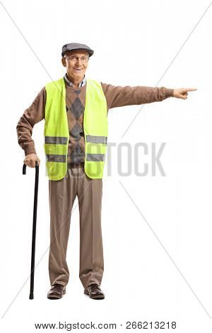 Full length portrait of an elderly man with a cane wearing safety vest and pointing in one direction isolated on white background