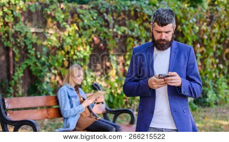 Man With Beard Hold Smartphone While Girl Sit Bench Park. Man Use Application For Dating. Guy Lookin