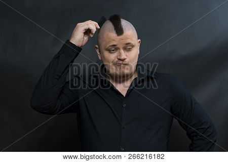 Subculture Punk. Iroquois. Goths. Young Man In His Right Hand Holds A Comb. Trying To Comb Your Hair
