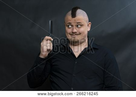 Subculture Punk. Iroquois. Goths. Young Man In His Right Hand Holds A Comb. Face Expresses A Sly And