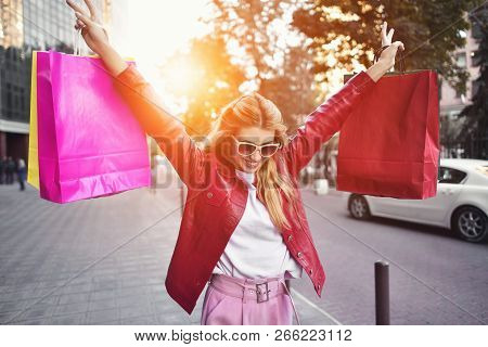 Beautiful Smiling Girl In Sunglasses Is Holding Shopping Bags And Enjoying Her Shopping.