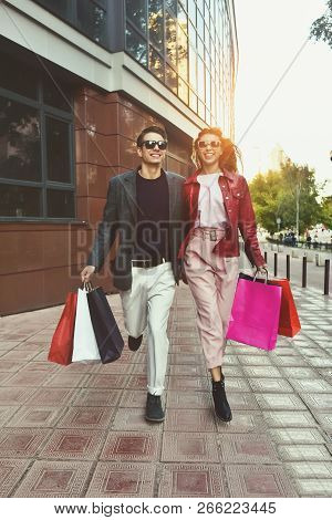 Couple In Shopping Together. Young Couple Holding Hands And Running Through Street.