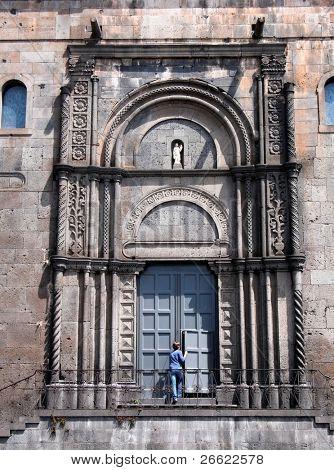 Randazzo young faithfull woman go into the church - old artistic portal of the basilica of Santa Maria