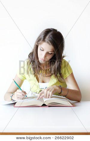 Menina estudante escreve Faça anotações do livro