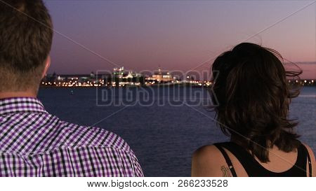 Man And Woman Standing On Pier. Scene. Close-up From Back Of Man And Woman Standing On Pier. Evening