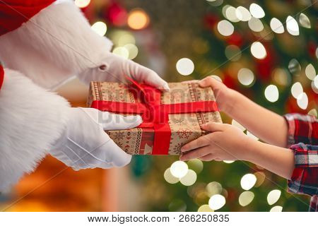 Merry Christmas and Happy Holidays! Hands of Santa Claus giving a x-mas gift to child.