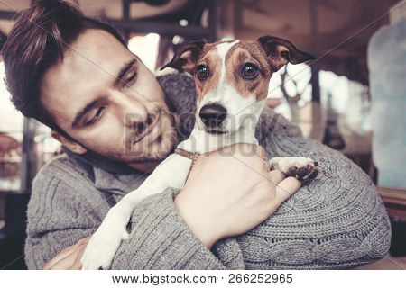 Man cuddling with his terrier dog in winter