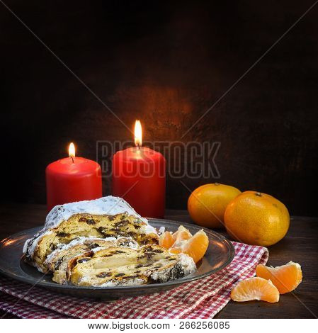 Christmas Cake, German Christstollen With Raisins And Marzipan In Front Of Two Red Candles And Tange
