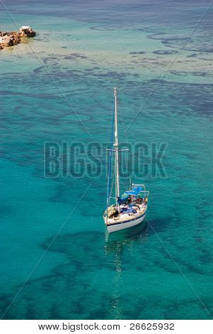 Aerial view of a sailing boat in transparent water of sea