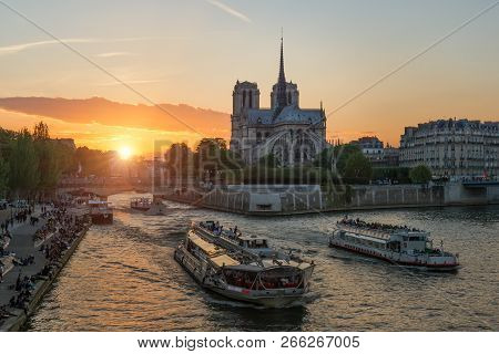 Notre Dame De Paris Cathedral With Cruise Ship In Seine River In Paris, France. Beautiful Sunset In