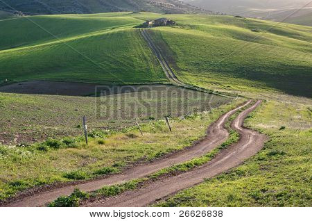 rural road to the old farm on the green hills at the twilight