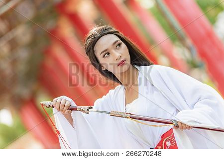 Beautiful Chinese Woman With A Traditional Suit With A Sharp Sword In Her Hands.