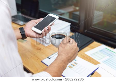 Business And Finance Concept, Businessman Holding Coffee Cup And Discussing Sale Analysis Chart In C