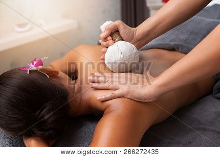 Asian Woman Enjoying Compress Balls, Herbal Ball Massage At Spa.