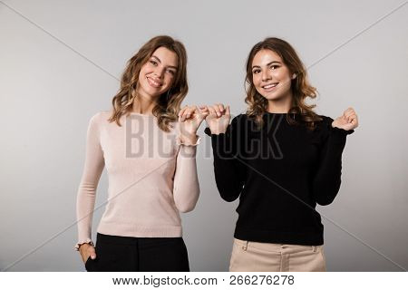 Image of two young women smiling and hooking each others little fingers in conciliation or friendship isolated over gray background