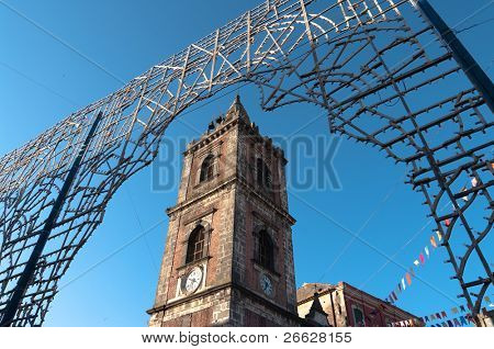 bell tower of holy Peter's church in Adrano - Italy -  under an arch of celebration