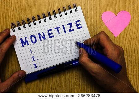 Text sign showing Monetize. Conceptual photo convert into or express in form of currency earn revenue from asset Man holding marker notebook page heart romantic messages wooden table. poster