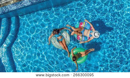 Aerial Top View Of Family In Swimming Pool From Above, Happy Mother And Kids Swim On Inflatable Ring