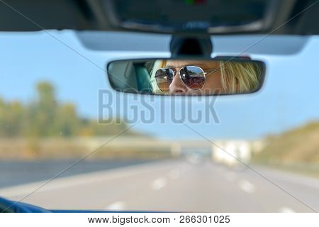 Woman Driving A Car On A Motorway With A View Ahead Through The Windscreen And Her Glasses Reflected