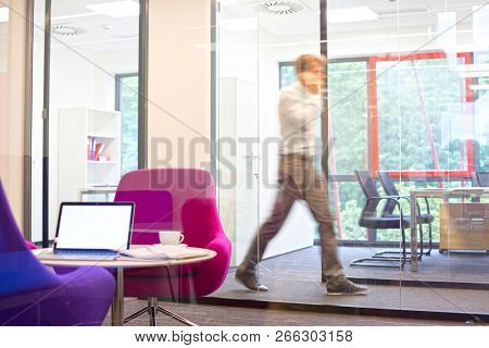 Business man on the telephone walking across the office in a blurred motion,laptop on a table in the foreground
