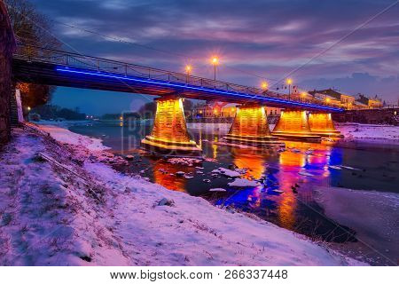 Pedestrian Bridge Through The River Uzh At Night. Beautiful Cityscape Of Old European Town Uzhgorod