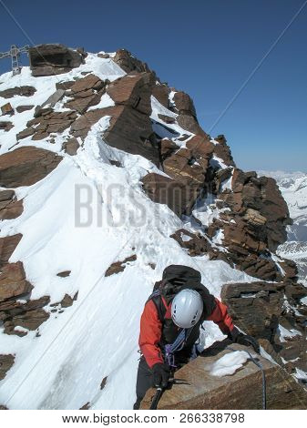 Mountain Climber On A Narrow Rock And Snow Ridge On His Way Down From A High Alpine Summit With A Me