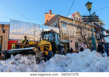Uzhgorod, Ukraine - January 19, 2017: Snow Removal On Streets Of Old Town. People Remove Snow Huge A