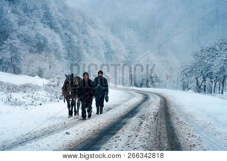 Kostryna, Ukraine - Dec 2, 2007: Two Men With A Horse On The Mountain Road In Winter. Horrible Weath