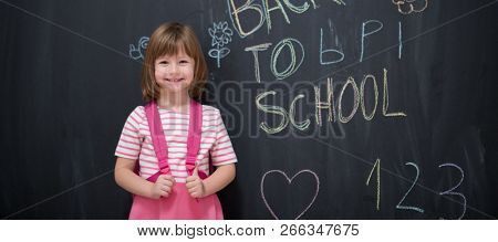 Happy school girl child with backpack writing  back to school on black chalkboard