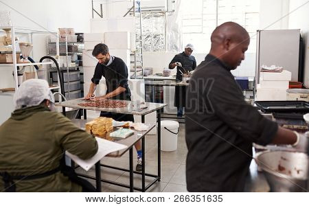 People working together in an artisanal chocolate making factory poster