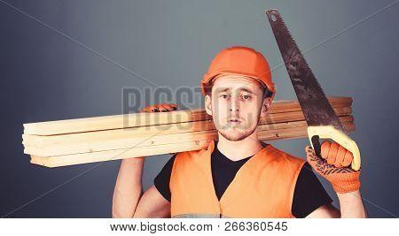 Man, Handyman In Helmet, Hard Hat Holds Handsaw And Wooden Beams, Grey Background. Carpenter, Woodwo