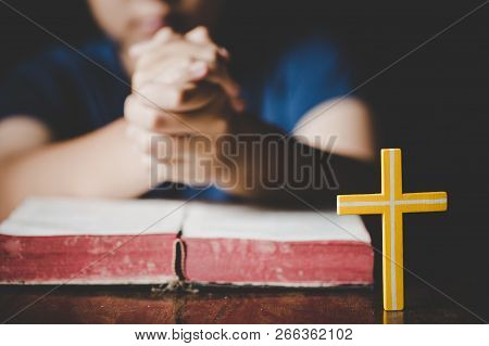 Woman Praying On Holy Bible In The Morning. Teenager Woman Hand With Cross And Bible Praying, Hands