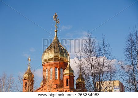poster of Old red brick Christian church in Kemerovo with golden and gilded domes against a blue sky and tree branches. Concept of faith in god, orthodoxy, prayer