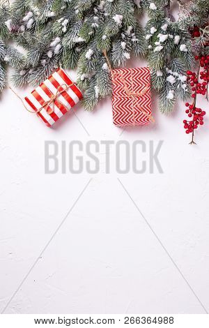 Border From Wrapped Christmas Presents, Fur Tree Branches, Red Berries On White Textured  Background