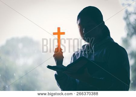Teenager Woman Hand With Cross And Bible Praying, Hands Folded In Prayer On A Holy Bible In Church C