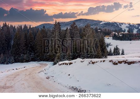 Wonderful Winter Countryside In Mountains At Dusk. Road Winds Down The Slope In To The Forest. Villa