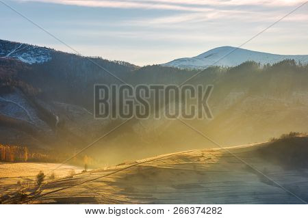 Rural Hill In Glowing Fog. Beautiful Autumn Scenery In Mountainous Area With Snowy Peaks In The Dist