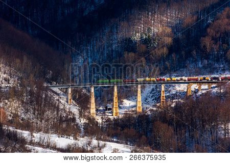 Winter Rail Road Transportation In Mountains. Freight Train With Colorful Carriage On The Old Viaduc