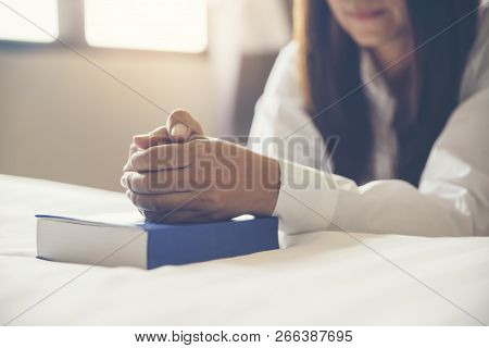 Beautiful Woman (christian) Hands On Bible,thinking And Closed Her Eyes At Bed Room.person Side View