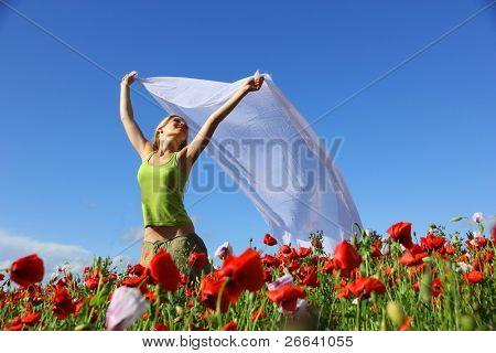 Happy blond girl running in poppy field
