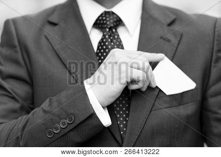 Closeup Of Man Hand Holds Business Card Over Suit Pocket Isolated On White. Businessman In Suit Draw