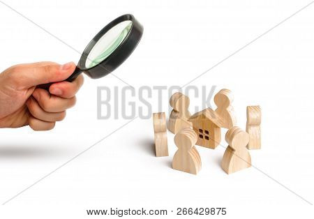 Magnifying Glass Is Looking At The Wooden Figurines Of People Stand Around The House. Search For A N