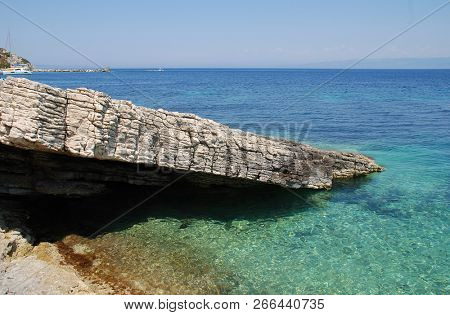 PAXOS, GREECE - JUNE 11, 2014: The rocky coastline of Levrechio beach at Loggos on the Greek island of Paxos. The 13km long island has a population of around 2300 people.