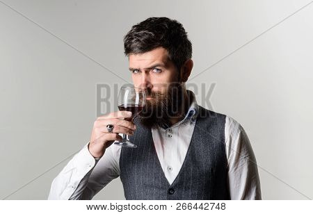 Handsome Businessman Is Drinking Red Wine With Enjoyment. Man In Waistcoat Holds Glass Of Red Wine.