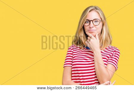 Beautiful young woman wearing glasses over isolated background looking confident at the camera with smile with crossed arms and hand raised on chin. Thinking positive.