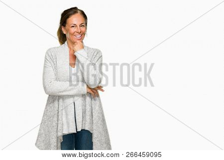 Beautiful middle age adult woman wearing winter sweater over isolated background looking confident at the camera with smile with crossed arms and hand raised on chin. Thinking positive.