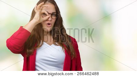 Beautiful plus size young business woman wearing elegant jacket and glasses over isolated background doing ok gesture shocked with surprised face, eye looking through fingers. Unbelieving expression.